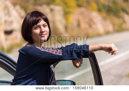 Young woman with auburn hair leaning on right passenger door of car on road and smiling