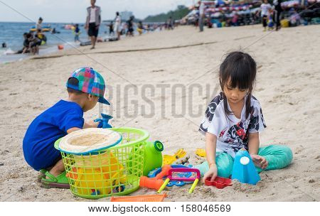 Asian kid are playing with sandbox on the beach
