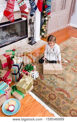 Small Girl Wrapping Christmas Gifts At Home
