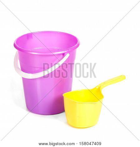 Yellow Plastic Ladle Near A Bucket