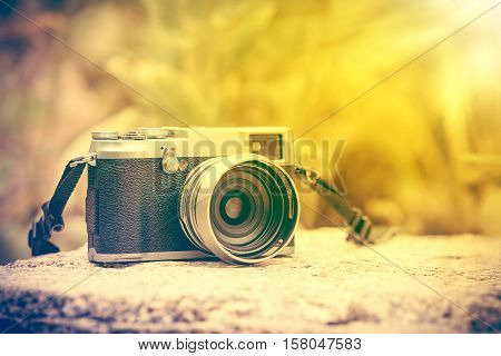 Vintage-style digital camera on boulder on blurred nature background outdoor at the daytime with bright sunlight. Shallow depth of field with focus on camera. Warm tone and vintage effect style.