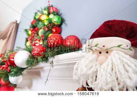 Woolly Face Of A Toy Santa Claus Below A Wreath