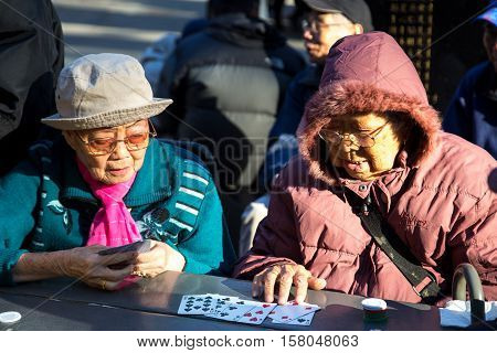 New York, United States of America - November 17, 2016: Two elderly Chinese ladies playing cards in Columbus Park in Chinatown
