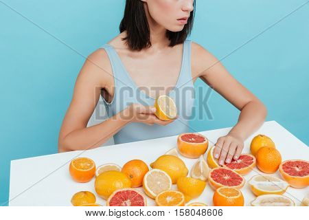 Beautiful young woman sitting and eating oranges and grapefruits at the table over blue background