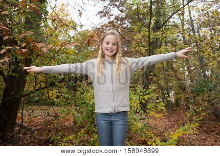 Cheerful And Happy Little Girl With Arms Outstretched Autumn