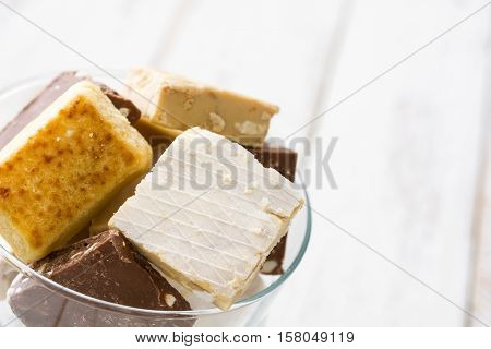 Variety of Christmas nougat in crystal glass on white wooden background