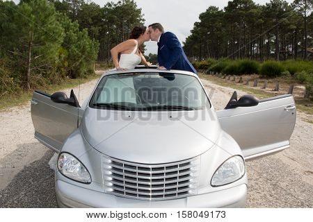 Kissing Wedding Couple Posing Near Cabriolet Car