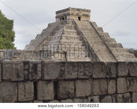 Chichen Itza, Mexico Mayan pyramid with stone wall in foreground