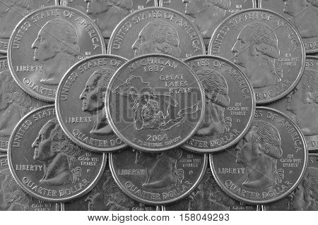 Coins of USA. Pile of the US quarter coins with George Washington and on the top a quarter of Michigan State.