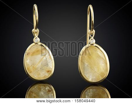Golden Earrings With Gemstone Isolated On Black Background
