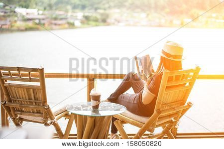 Woman reading a book lying and drink ice coffee on the chair