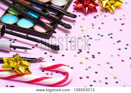 Makeup for holiday party. Red lipstick, liquid eyeliner, mascara, color glitter eyeshadow, brushes and applicator with candy cane, gift wrap bows and confetti. Shallow depth of field. Copy space