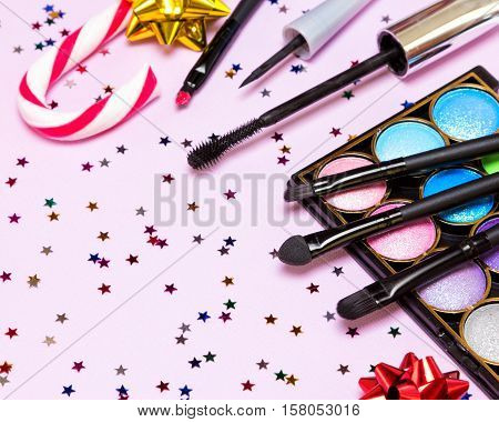 Makeup for holiday party. Color glitter eyeshadow, mascara, eyeliner, red lipstick, applicator, brushes with candy cane, gift wrap bows and star shaped confetti. Shallow depth of field. Copy space