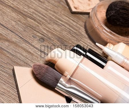 Foundation makeup products as frame. Liquid and cream foundation, concealer, powder, makeup brushes. Selective focus, copy space