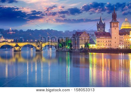Famous Prague Landmarks at night time with city illuminated and beautiful sundown sky, Czech, Europe
