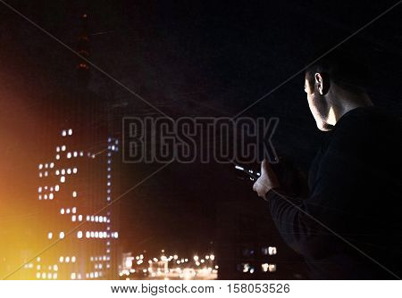 Filtered high-iso Image of photographer looking for night city street. View from skyscraper
