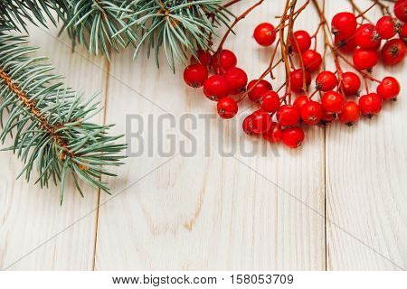 Christmas mokup.Tree branch frame with rowanberry .White wooden table.Top view