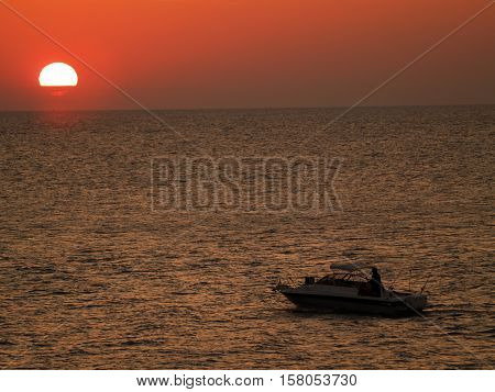 Lone fishing boat against the sun low on the horizon