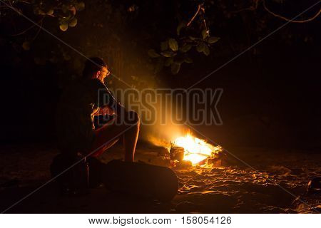 Image of a large campfire, around which people basking in the mountains at night.