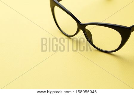 Glasses in empty yellow background