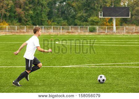 Boy playing football at stadium