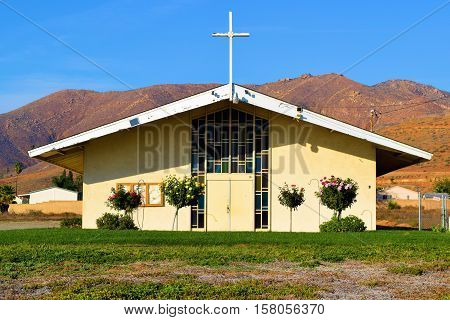 Old community chapel which is an oasis in the desert with a green lawn and barren brown mountains beyond