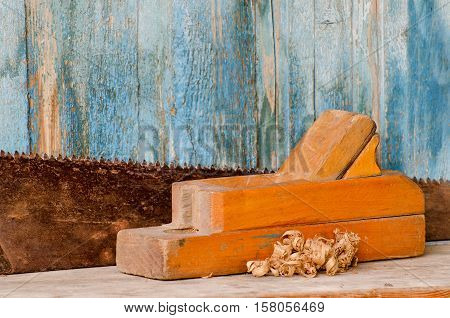 Old wooden planer and saw on vintage background close-up