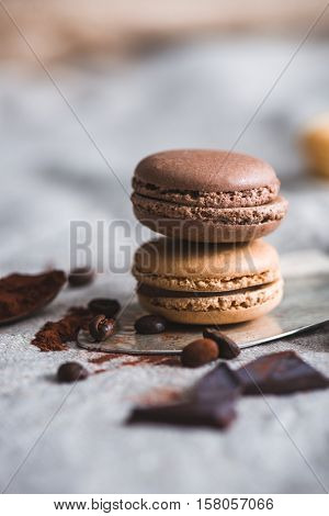 Chocolate and coffee French macarons, with cocoa powder, coffee beans and chocolate pieces around. Closeup shot