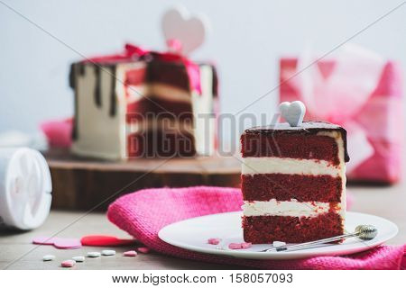 Closeup shot of a piece of a cake with Valentine Day heart shaped decoration around