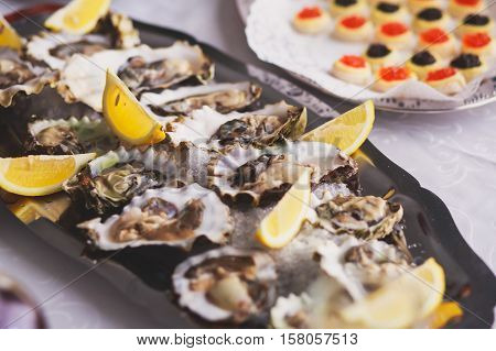 Beautifully decorated catering banquet table with caviar, oysters, mussels and seafood with ice and lemon on corporate christmas birthday party event or wedding celebration