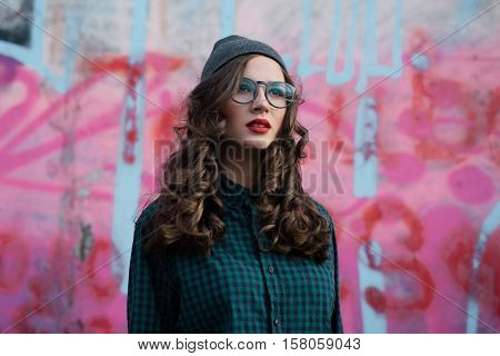 curly girl with transparent glasses, pink backround and graffitti