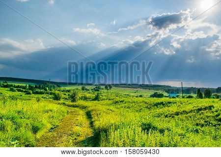 Sun rays at storm sky under a valley