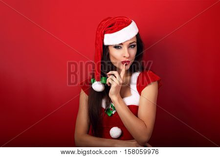 Sexy Woman In Santa Claus Christmas Costume Showing The Finger The Silence Sign On Bright Red Backgr