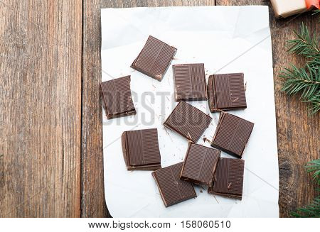 Dark chocolate bar broken in on the wooden table. Christmas decoration
