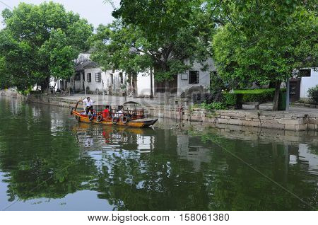 July 25 2015. Tongli Town China. A wooden tourist boat moving by Chinese architecture on the water canals within Tongli Town scenic area in Jiangsu Province China.