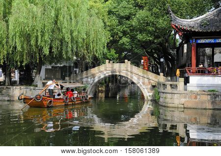 July 25 2015. Tongli Town China. A tourist boat moving by Chinese architecture towards an arched bridge on the water canals within Tongli Town scenic area in Jiangsu Province China.