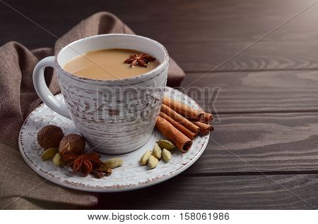 Indian masala chai tea. Spiced tea with milk on the rustic wooden table. Selective focus, horizontal with copy space.