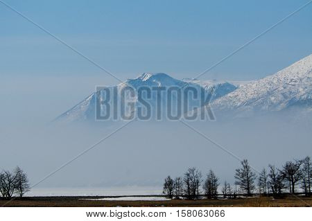 Atmospheric clouds linger around the peaks of the Sayany after a spring snow storm.