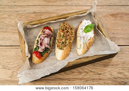 Three different delicious sandwiches lying on paper in box