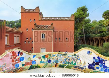 Park Guell in Barcelona. View on red pavilion with mosaics on foreground