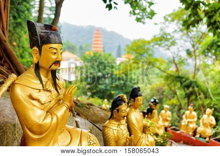 Golden Buddha Statues On Background Of A Red Pagoda And Forest In Hong Kong