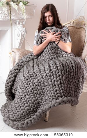Girl with large grey knit blanket giant knit blanket super chunky yarn arm knitting