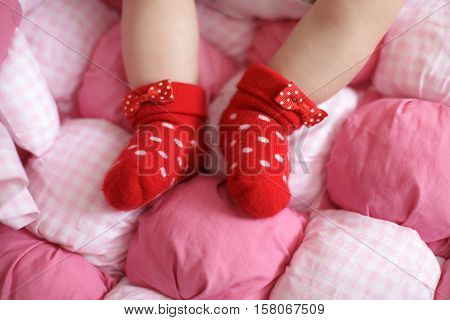 Close up of babies feet wearing red cotton socks, pink background, selective focus