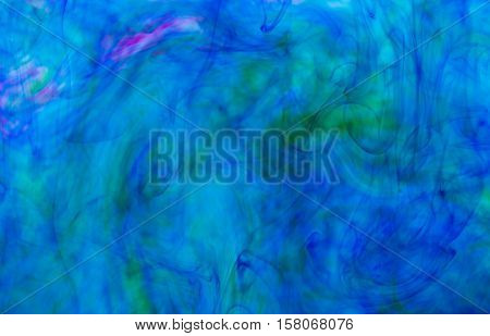Abstract underwater color background. Color drop underwater creating a silk drapery. Ink swirling underwater. Blue and green