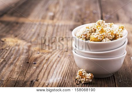 Roasted cashew nuts coated with a honey glaze and sprinkled with white sesame seeds in white ceramic dishes a la carte on a simple wooden background. Garnish to the cheese plate appetizer, aperitif, in horizontal design. selective focus