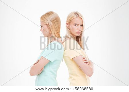 Portrait of two indignant girls standing back to each other with arms crossed. Isolated over white background.