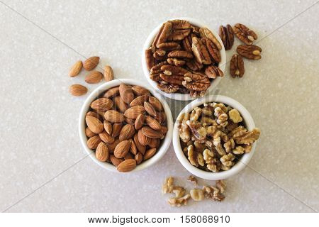 Almonds, pecans, and walnuts in containers on a kitchen countertop. Photographed from above with containers centered.
