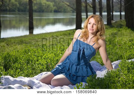 blonde girl lying in the park with tablet on the red coverlet. summer