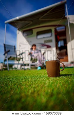 Coffee Mug on grass. Caravan car Vacation. Family vacation travel, holiday trip in motorhome