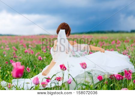 Beautiful happy bride in white dress having fun in flower poppy field on summer day. Just married, young amazing woman laughing, smiling. Happiness, family, wedding concept